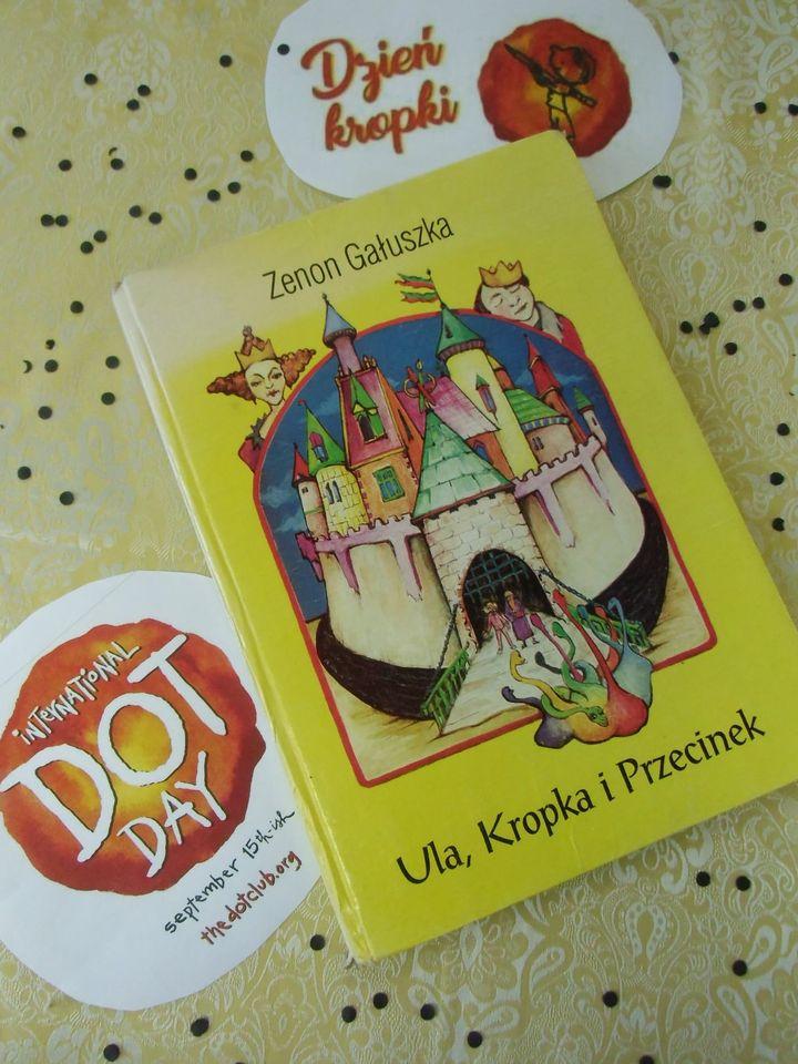 """Na zdjęciu książka """"Ula, Kropka i Przecinek"""" - Zenona Gałuszki. Okładka książki w kolorze żóltym, na okładce zamek. W tle widać królową i króla. Obok ksiązki jest napis Dzień Kropki, obus w kolorze piaskowym, na którym rozsypane są czarne kropki"""