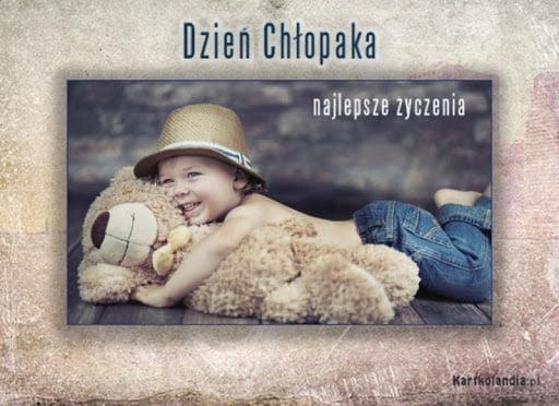 Kartka z życzeniam na Dzień Chłopaka. Kartka w kolorze beżowym, na środku zdjęcie chłopca, który przytula pluszowego misia