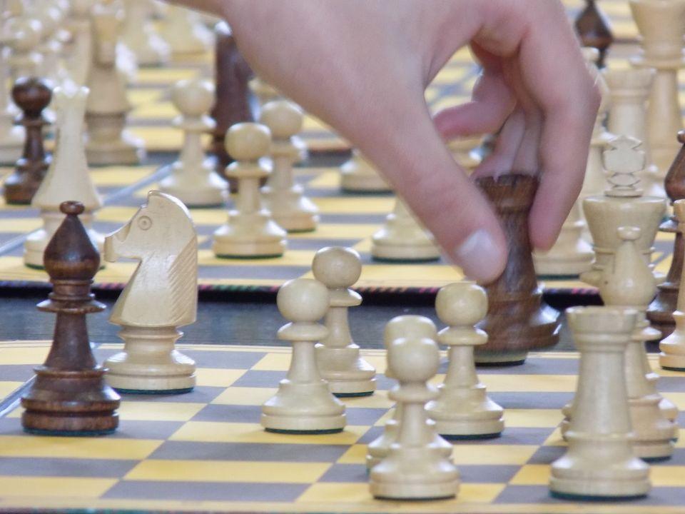 Na zdjęciu szachownica i dłoń osoby, która wykonuje ruch