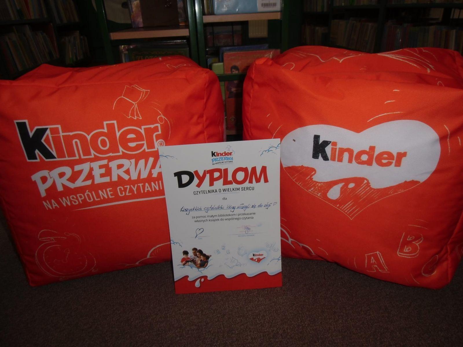 Na zdjęciu dwie pufy z akcji Kinder Mleczna Kanapka - Przerwa na Wspólne Czytanie w kolorze pomarańczowym, między pufami, na środku zdjęcia dyplom dla czytelników, którzy przynieśli książki, w tle regały z ksiązkami