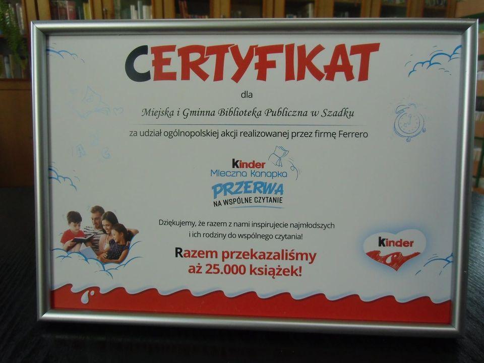 Certyfikat dla Miejskiej i Gminnej Biblioteki Publicznej w Szadku za udział w ogólnopolskiej akcji realizowanej przez firmę Ferrero. Certyfikat na białym tle, w srebrnej ramie. Grafika w kolorach czarno-biało-niebieskim. Po lewej stronie, rodzice z dwójką dzieci wspólnie czytają książkę, po prawej stronie serduszko z grafiką Kinder.