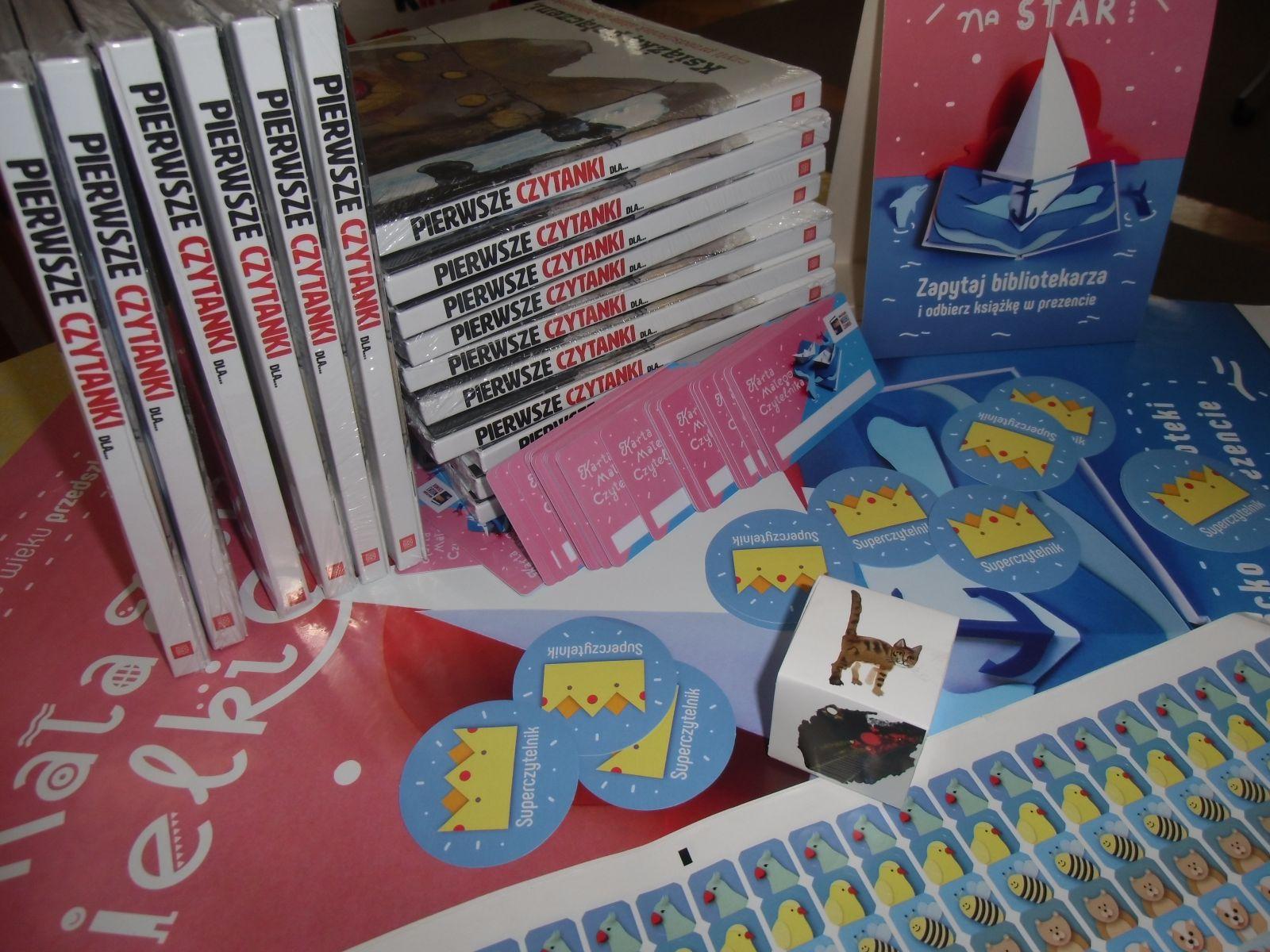 """Na zdjęciu  książki """"Pierwsze czytanki dla..."""", Karty Małego Czytelnika w kolorze różowo-niebieskim, na których jest niebieska książka, a na niej pływają dwie łódki zrobione metodą origami, wokół książki pływają dwa delfiny, kolorowe naklejki ze zwierzętami i owadami"""
