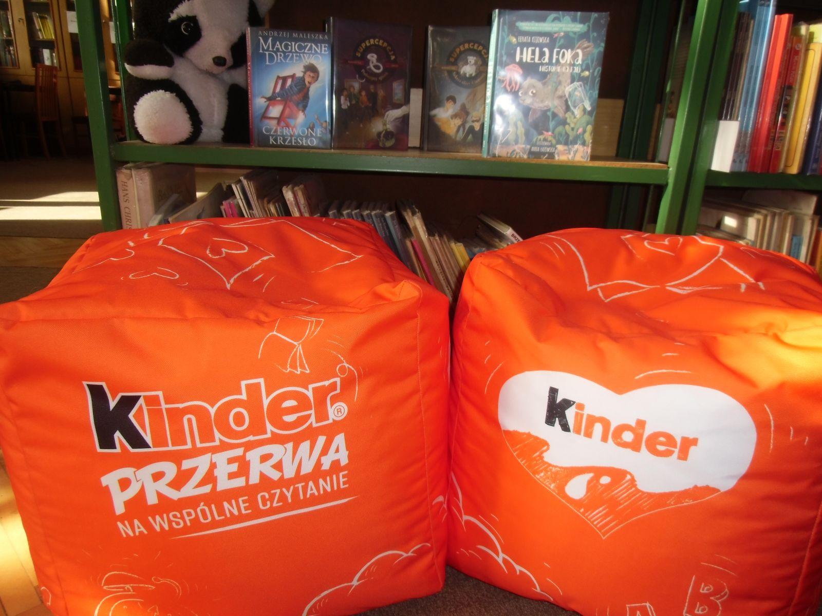 """na zdjęciu dwie pomarańczowe pufy z logo akcji """"Kinder Przerwa Na Wspólne Czytanie"""". W tle regał z książkami"""