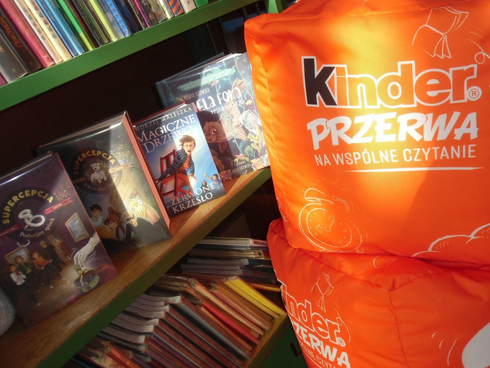 Na zdjęciu po prawej stronie dwie pufy położona jedna na drugą w kolorze pomarańczowym, po lewej stronie regał z książkami dla młodzieży.